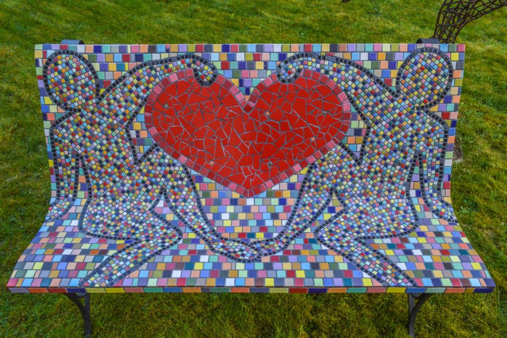 Banc en mosaïques multicolores. 2 personnages qui tiennent un grand coeur rouge.
