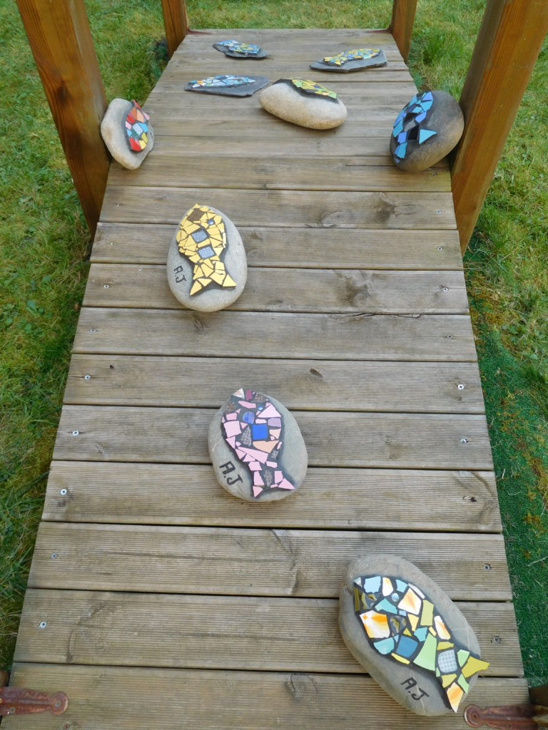 Mosaïques sur galets, poissons, exposés dans le patio de la Maison de Retraite.