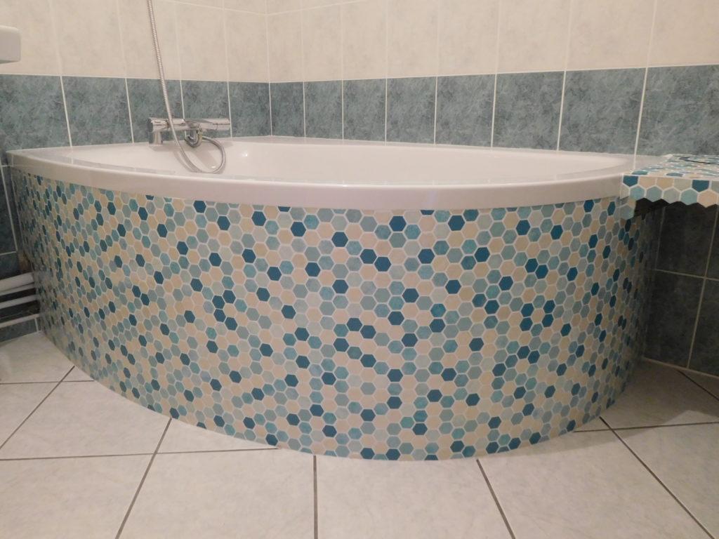 Baignoire arrondi, habillage en mosaïques hexagonales, bleus et blanc.