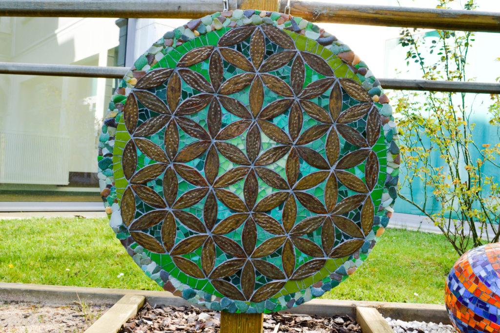 Mandala végétal réalisé avec des pétales en céramique, du verre, et des pierres de laplage, dan les couleurs verts.