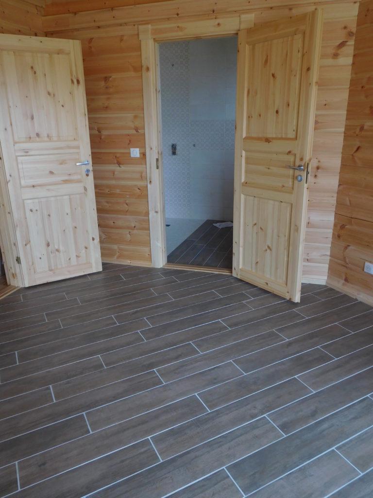 Pose de carreaux imitation plancher, couleur brun bois.