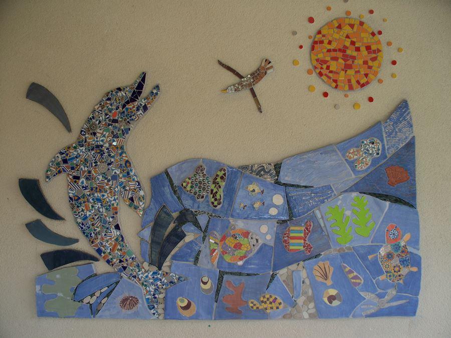 """Fresque en mosaïques sur le thème """"la mer"""", avec poissons, dauphin, coquillages, soleil. Réalisé avec des élèves de maternelle."""